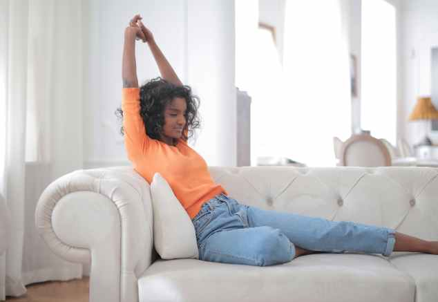 woman in orange top and blue denim jeans sitting on white couch